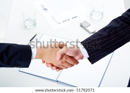 Woman and man shaking hands over paper, pen, phone, glasses