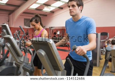 Woman and man stepping on step machines in gym