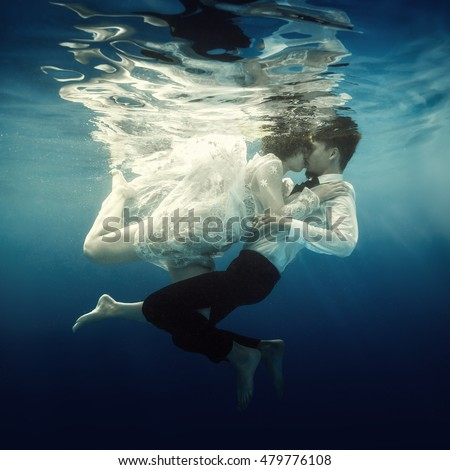 Woman and man swimming underwater #479776108