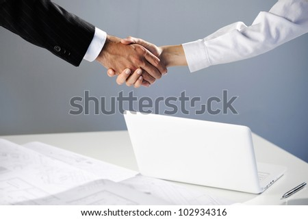 Woman and men shaking hand, laptop on background