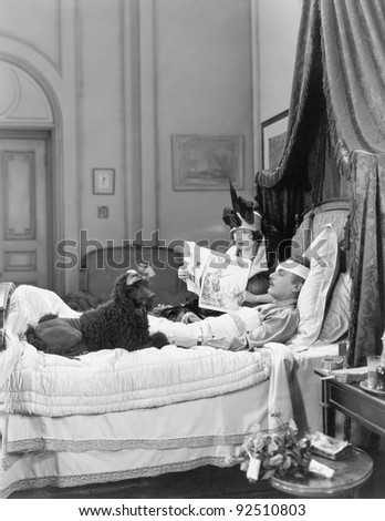 Woman and poodle sitting next to an injured man in bed