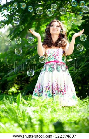 Woman and soap bubbles in park - stock photo