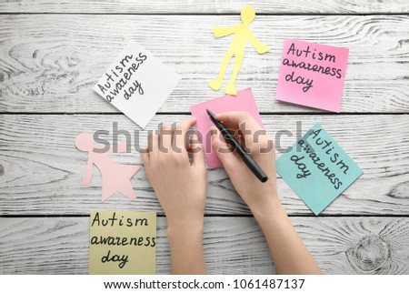 "Woman and sticky notes with phrase ""Autism awareness day"" on wooden background #1061487137"