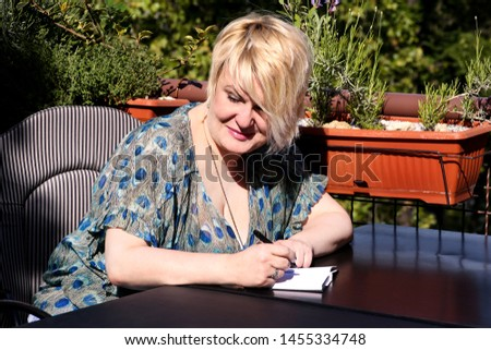 Woman and student sitting at table in bar, takes notes in notebook, learning and writes thoughts, writes book, she is preparing his exams doing homework and thinking, writing something in notebook.
