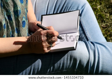 Woman and student sitting on grass, takes notes in notebook, learning and writes thoughts, writes book, she is preparing his final exams doing homework and thinking, writing something in his notebook.