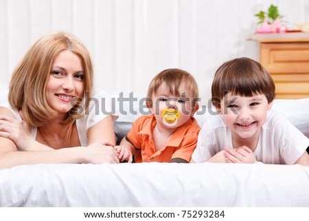 Woman and two children lying on bed