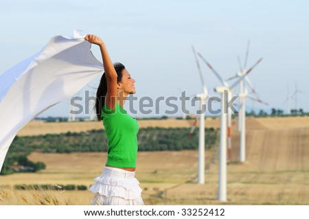 woman and wind, electronic power and alternative energy between turbines and windmill - stock photo