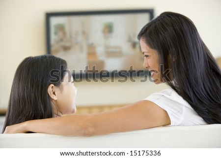 Woman and young girl in living room with flat screen television smiling