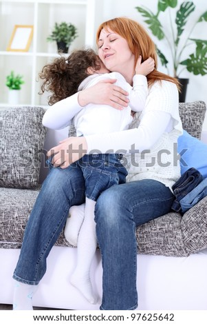 Woman and young girl sitting in living room and embracing