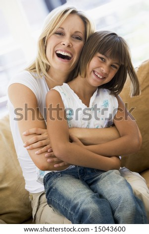 Woman and young girl sitting in living room smiling
