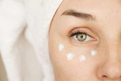 woman applies cream against wrinkles
