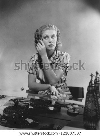 Woman applies makeup at her dressing table