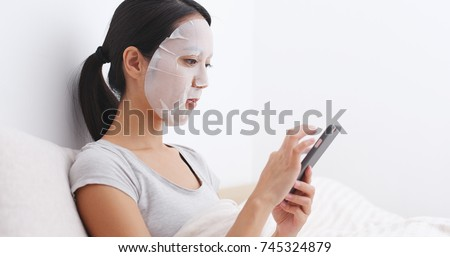 Woman apply facial mask and using cellphone on bed