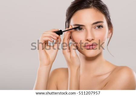 Shutterstock Woman applying black mascara on eyelashes with makeup brush. Young beautiful woman applying mascara makeup on eyes by brush. Portrait of brunette beauty girl applying makeup over grey background.