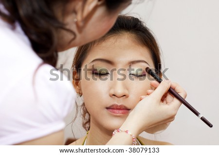 Woman applying cosmetic with applicator. Make-up treatment.