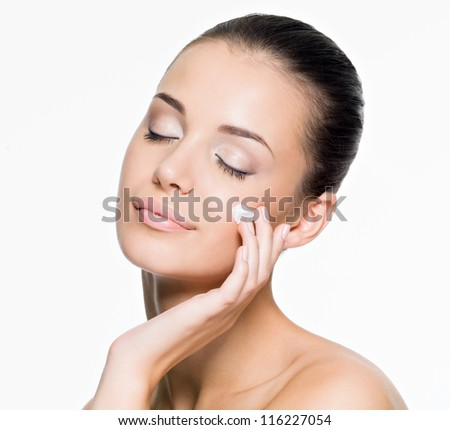 Woman applying cream on face - isolated on white