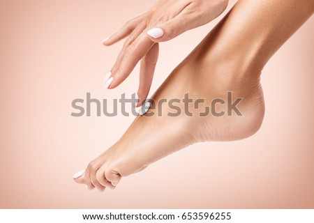 Woman applying cream on her beautiful feet. #653596255