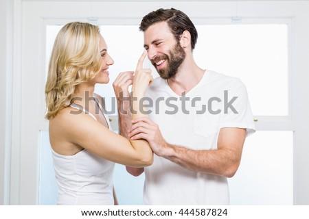 Woman applying cream to her man in bathroom