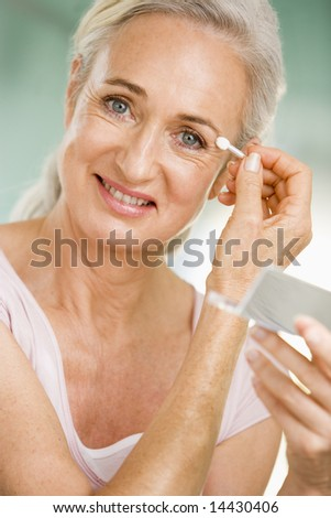 Woman applying eye makeup and smiling