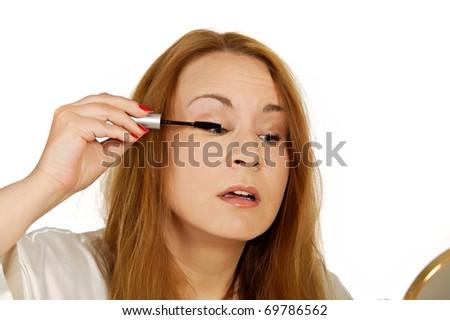 Woman applying eye makeup.  Shot in studio on white background.