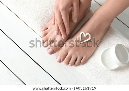 Woman applying foot cream on white wooden floor, closeup with space for text. Spa treatment Stockfoto ©