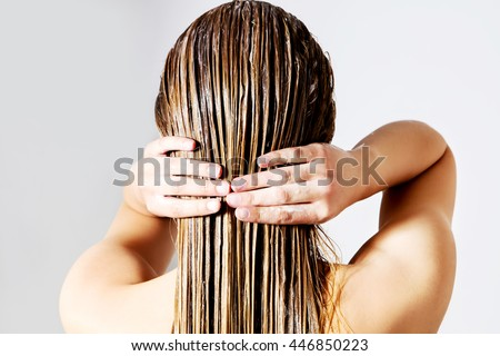 Woman applying hair conditioner. Isolated on white. #446850223