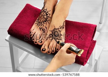 Woman applying henna on female foot #539767588
