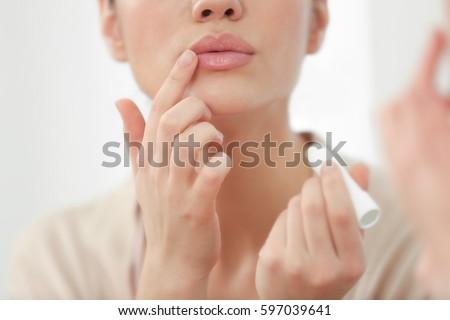 Woman applying hygienic lip balm near mirror #597039641