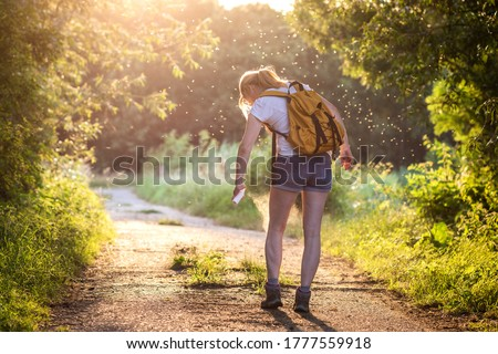 Photo of  Woman applying insect repellent against mosquito and tick on her leg during hike in nature. Skin protection against insect bite