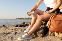 Woman applying insect repellent onto leg at beach, closeup. Space for text