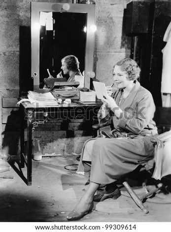Woman applying lipstick in her dressing room