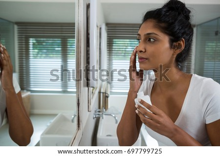 Woman applying lotion in bathroom at home