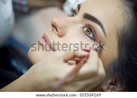 Woman applying mascara on her long eyelashes