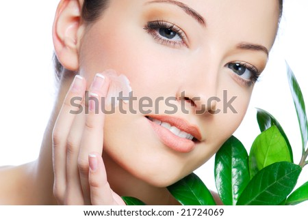 stock photo : Woman applying moisturizer cream on face.
