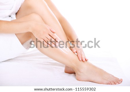 Woman applying moisturizer cream on the legs over white background
