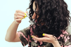 Woman applying natural oil on the tips of her curly hair, close up. Curly woman using serum for hair at home. Healthy curly hair. Natural products and cosmetics for hair.