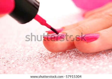 Woman applying pink nail polish