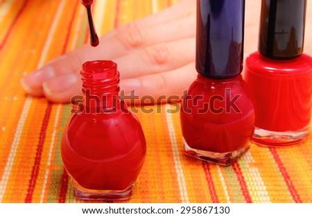 Woman applying red nail polish, manicured nails of woman, nail care