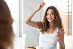 Woman Applying Serum For Hair Repair Looking At Mirror Standing In Modern Bathroom At Home. Damaged And Split Ends Haircare Treatment Concept. Selective Focus
