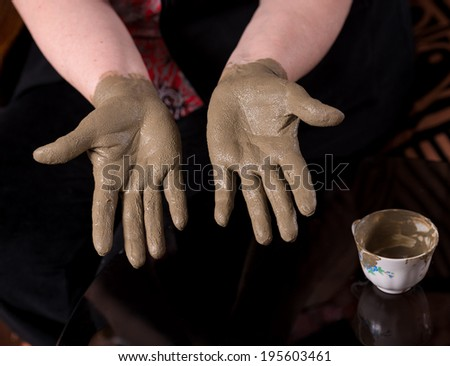 Woman applying spa cosmetic clay cream on hands