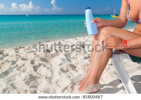 Woman applying sun blocker on the beach - stock photo