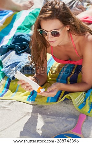 Woman applying sunscreen at the beach wearing bright pink bikini and lying on blue and green striped beach towel