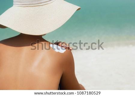 Woman applying sunscreen creme on  tanned  shoulder. Skincare. Body Sun protection suncream. Bikini hat woman applying moisturizing sunscreen lotion on back. #1087180529