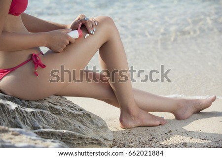 Woman Applying Sunscreen Lotion on Her Sexy Legs at Beach #662021884