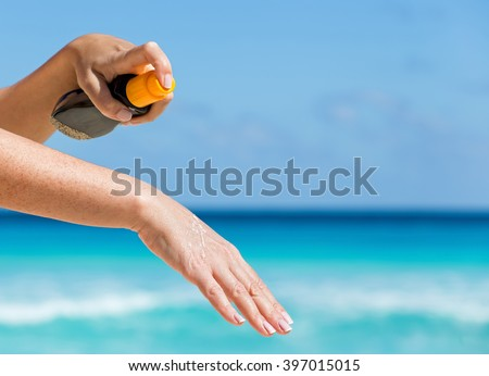Woman applying sunscreen protection cream against turquoise caribbean sea water and blue sky. Tropical summer vacation concept #397015015