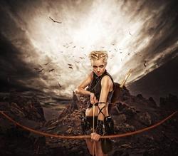 Woman archer against storm over rocks