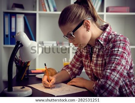 Woman architect working at construction project late at home. Young female executive having deadline.