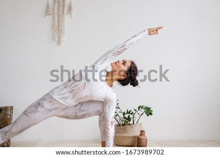 Woman are doing yoga in home.