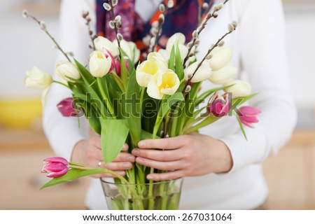 Woman arranges spring flower bouquet in a vase