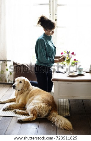 Woman Arranging Flowers with Golden Retriever Dog Laying
